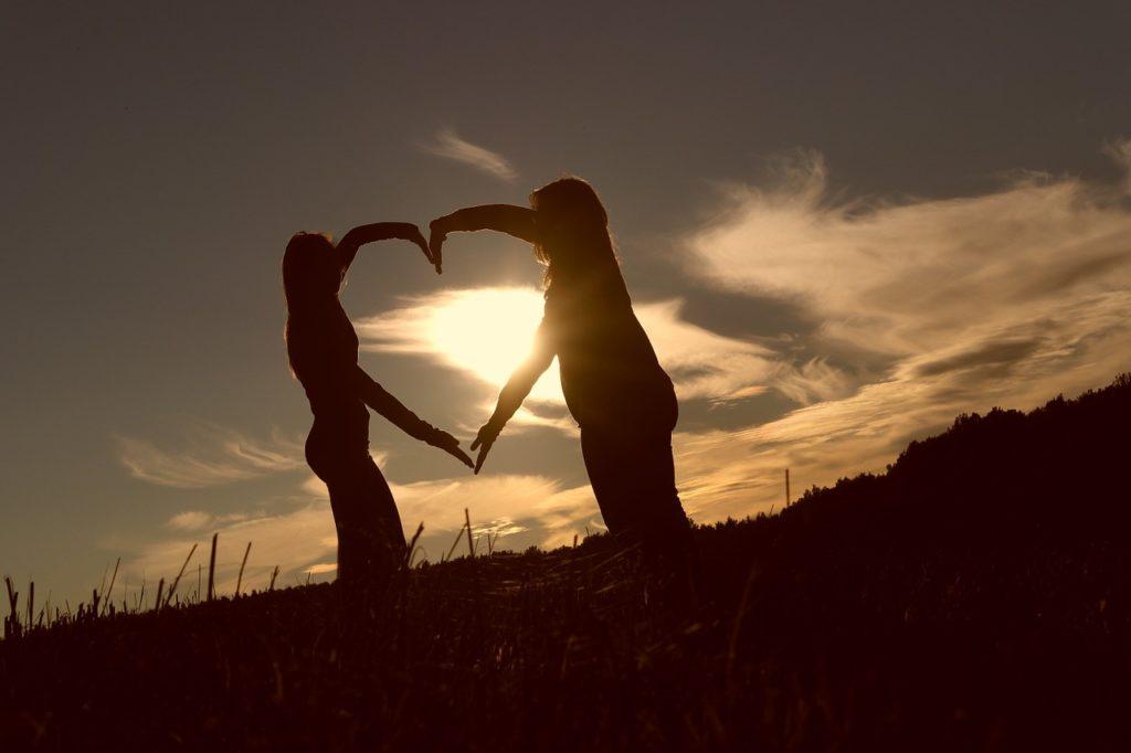 due persone uniscono le braccia a forma di cuore davanti al tramonto