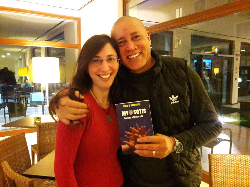 Abbraccio tra il Dott. Roy Martina ed Elisa k Staderini mentre tengono in mano il libro Myosotis, insieme vita dopo vita