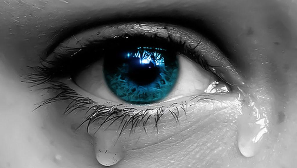 un occhio azzurro in primo piano che lacrima