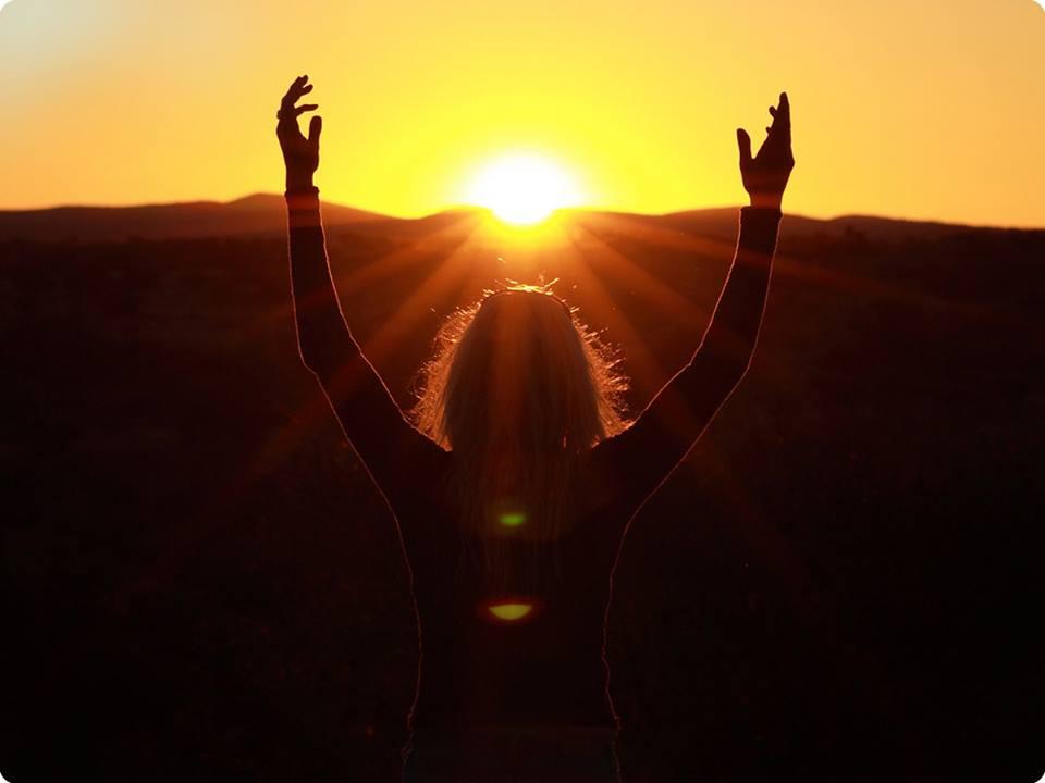 una donna alza  le braccia di fronte al sole e viene investita dai raggi solari