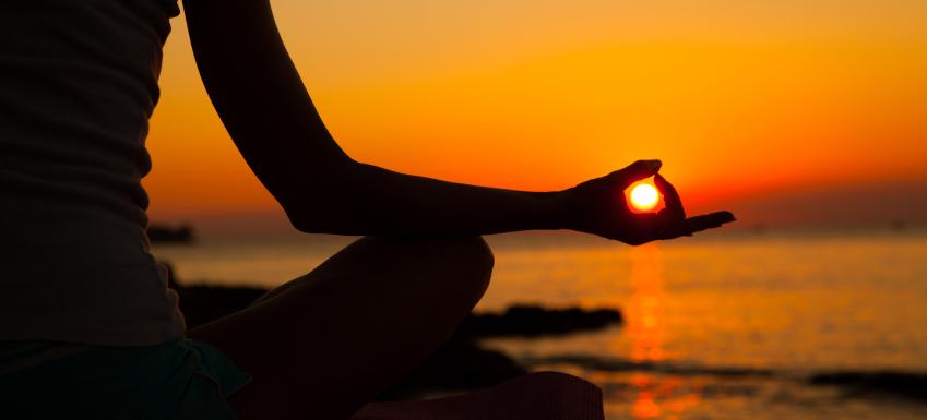 una donna fa yoga e nella mano sembra che tenga il sole