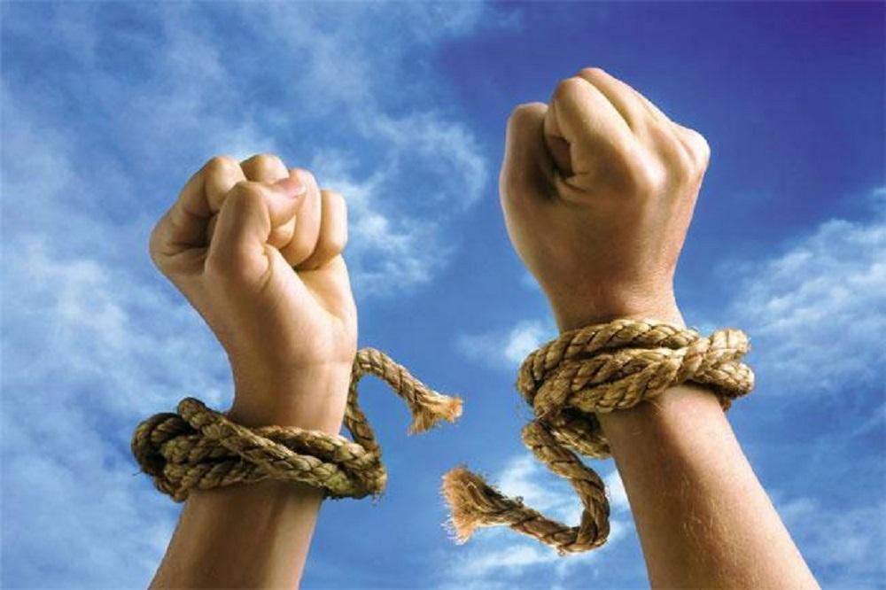due braccia che si liberano strappando le corde ai polsi su uno sfondo di cielo azzurro