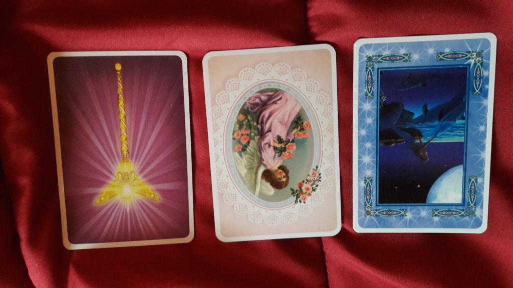 su un panno rosso ci sono tre carte oracolari disposte per la lettura