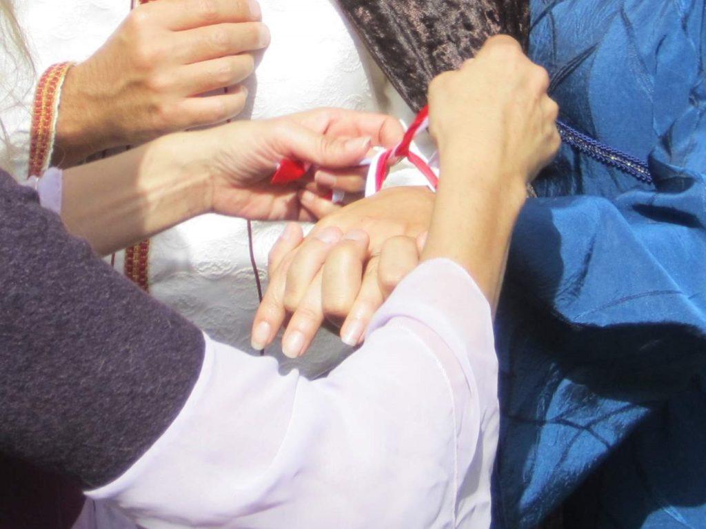 un bracciale bianco e rosso per unire le mani degli sposi nel rito celtico