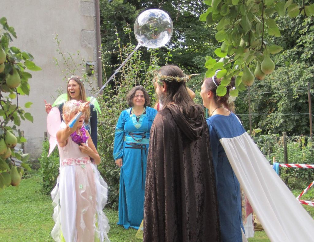 la sposa e lo sposo con i mantelli magici, la celebrante in abiti fatati e le madrine con le ali da fata immersi nel verde