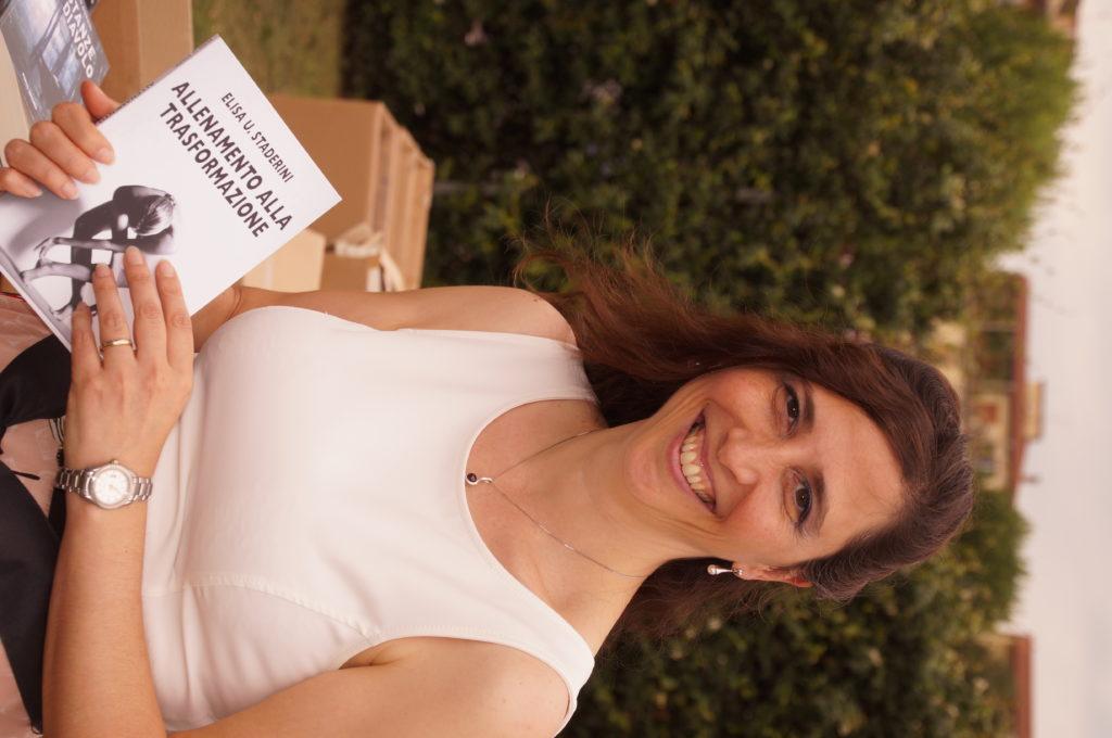 Elisa Staderini il giorno della presentazione del suo Allenamento alla Trasformazione. In primo piano con il libro in mano e sullo sfondo vegetazione verde