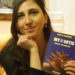 Elisa k Staderini Light Coach con in mano il suo romanzo Myosotis sulle vite passate