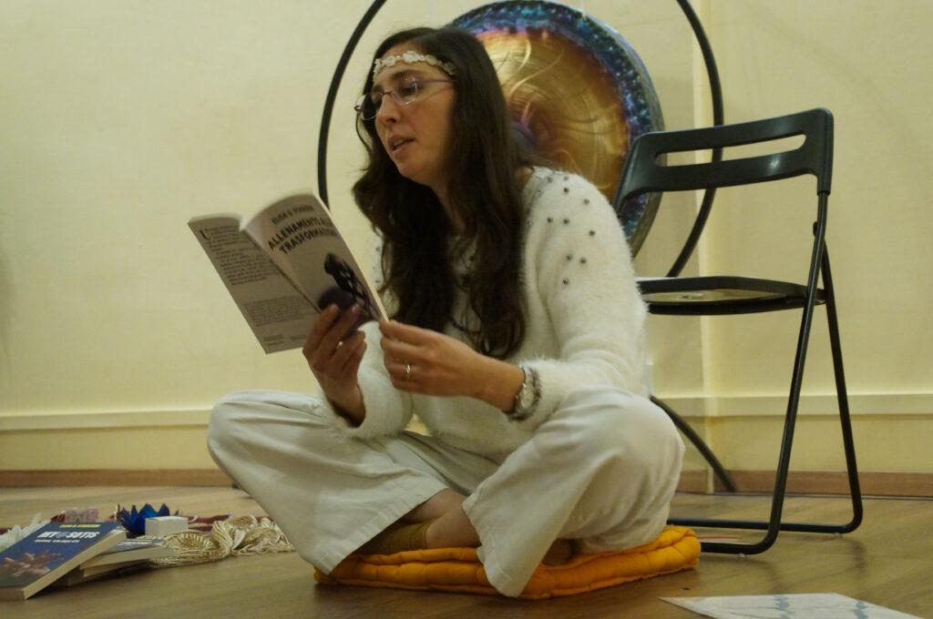 Elisa Staderini vestita di bianco seduta per terra a gambe incrociate, durante una delle presentazioni pubbliche di Allenamento alla Trasformazione