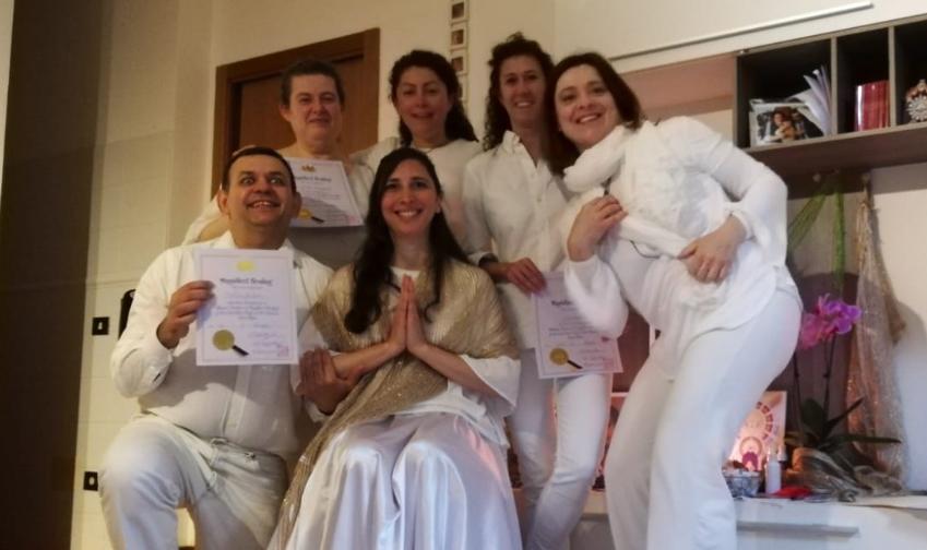 un gruppo di persone vestite di bianco intorno a Elisa k Staderini insegnante di Magnified Healing