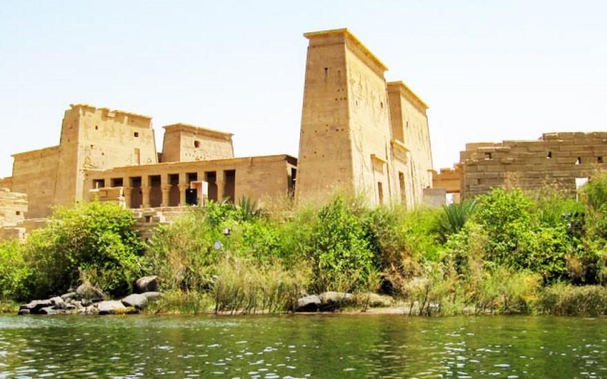 tempio di iside con in primo piano verdi piante e il fiume che scorre