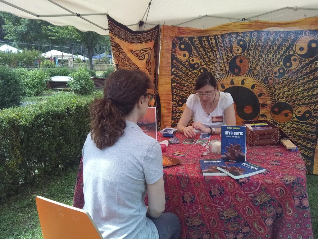 elisa k staderini legge le carte per una donna seduta di fronte. Si trovano allo stand di esistenza durante un festival del benessere