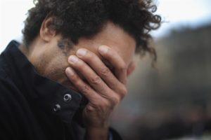 un uomo che si nasconde il volto mentre piange